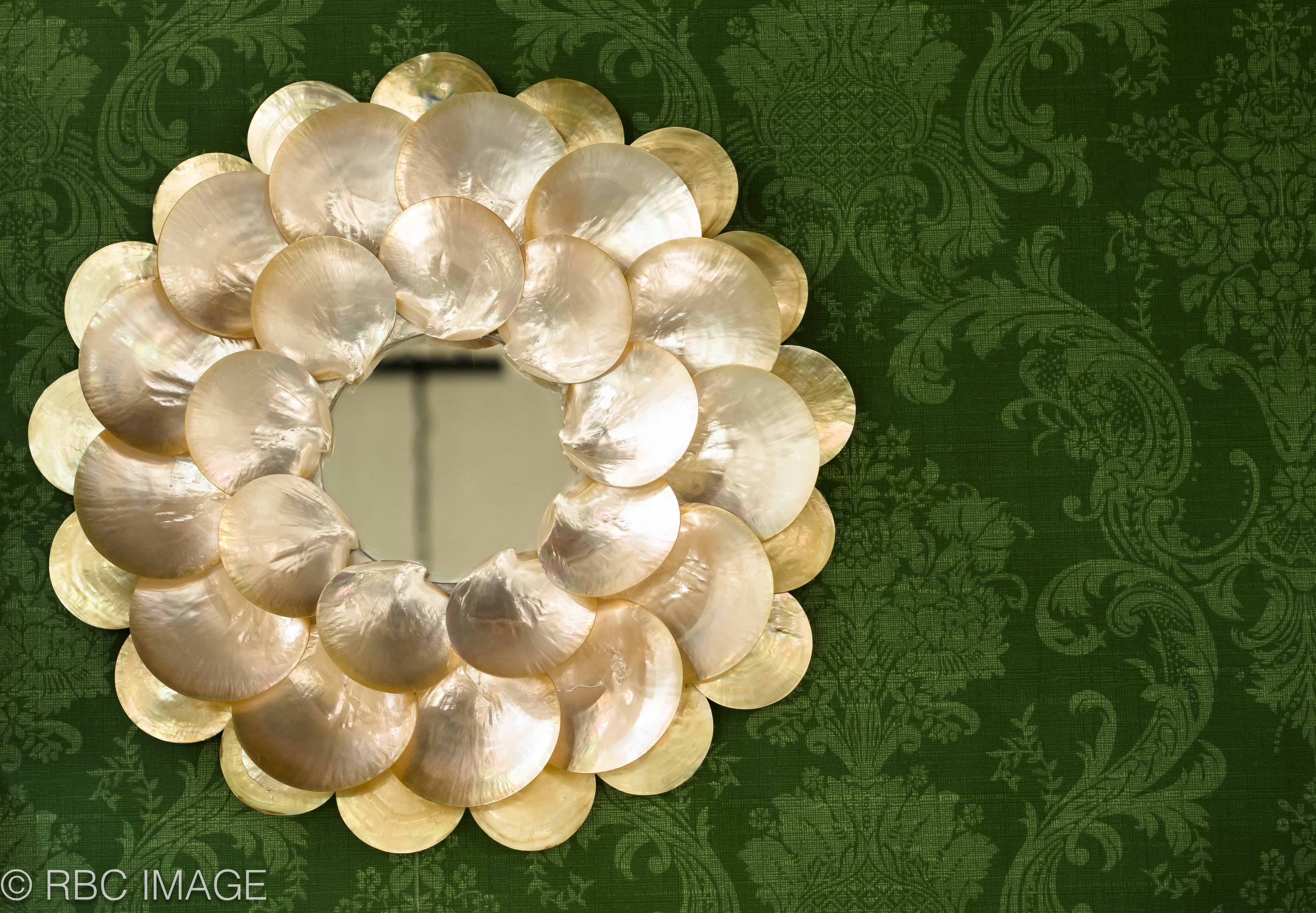 a mirror encircled in seashells
