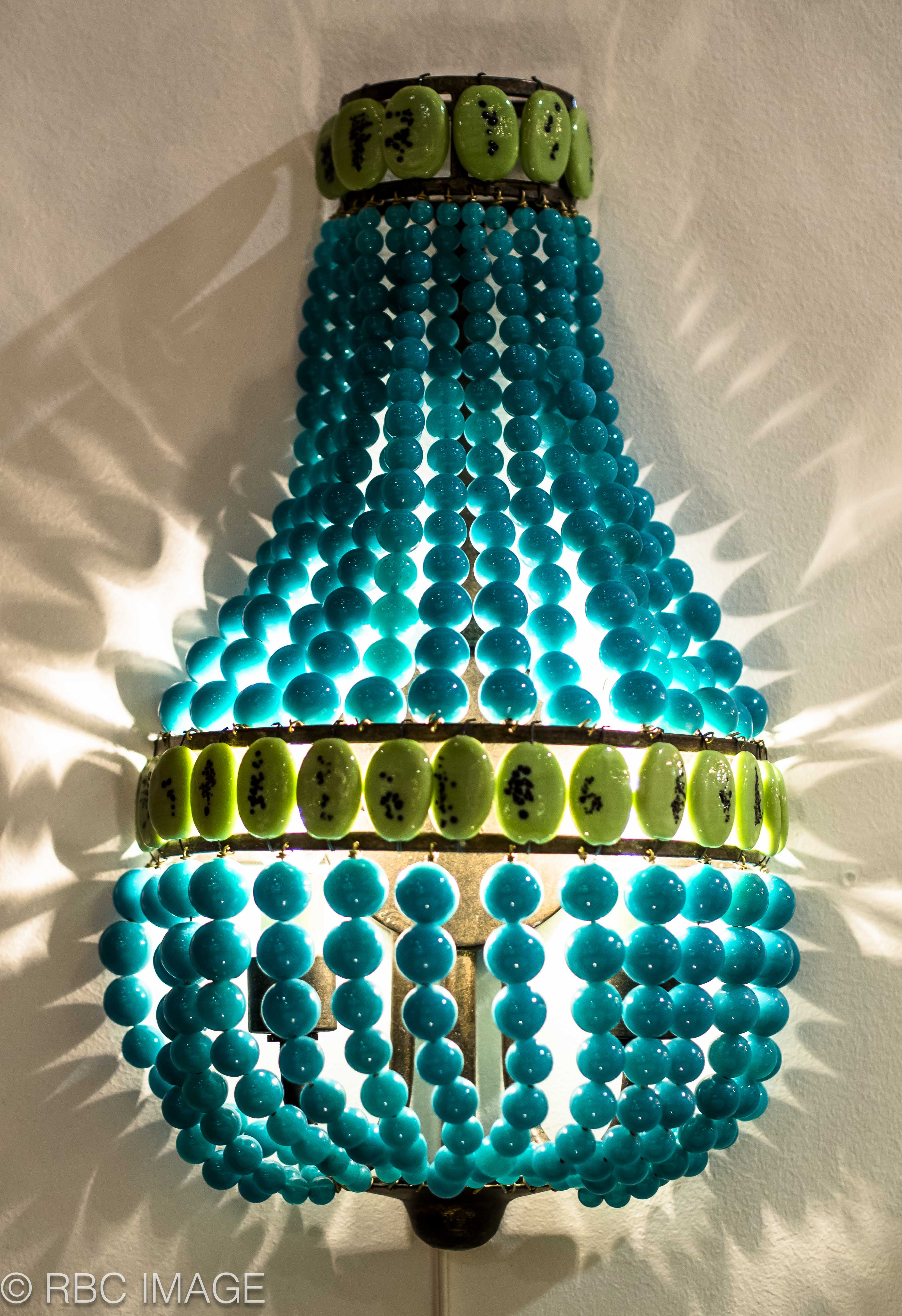 An image of one of our colorfully beaded wall sconces from the showroom.