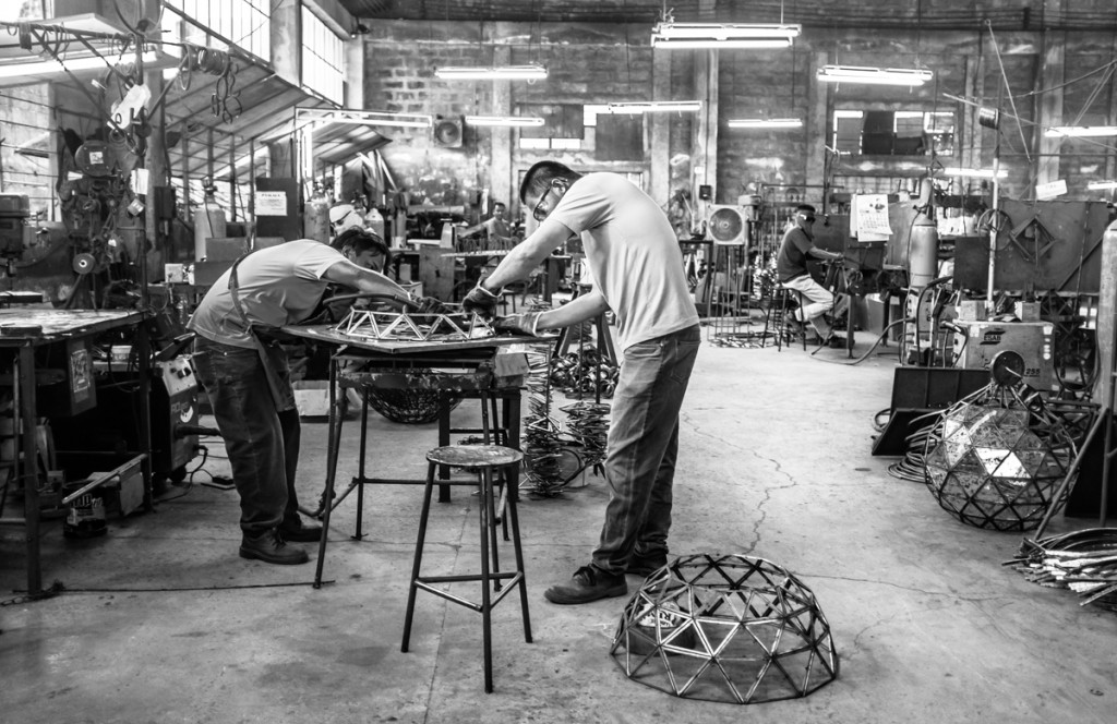 two workers struggle with the alignment of the Buckminster chandelier