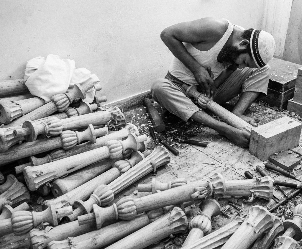 A man carving wooden posts by hand, the craftsmanship in each piece remarkable