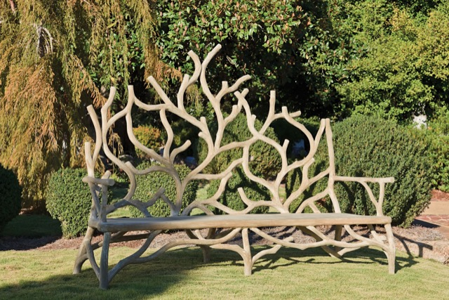 The faux bois Elwynn bench set within a lush garden