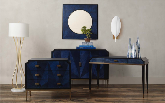 The Currey & Company Kallista family of furniture with a luminous dark blue chest, credenza, desk and mirror.