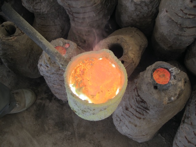 Molten bronze being poured into the mould, the result will be a finely crafted artisanal sculpture.