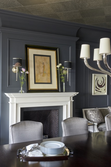 A dining room with our Primo Black Nickel Wall Sconce flanking the art above the fireplace.