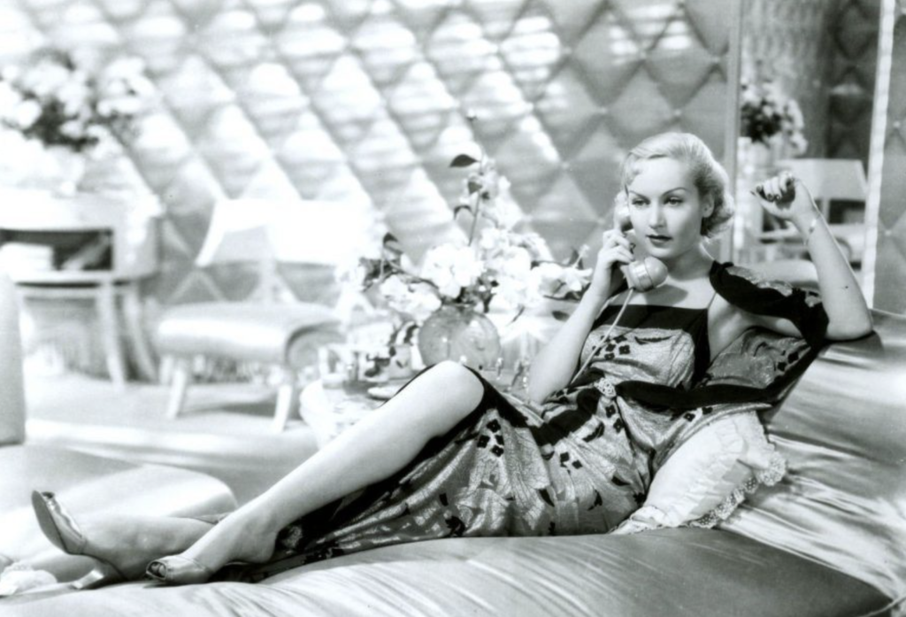 Carole Lombard reflects the glamour of her surroundings. Image in public domain.