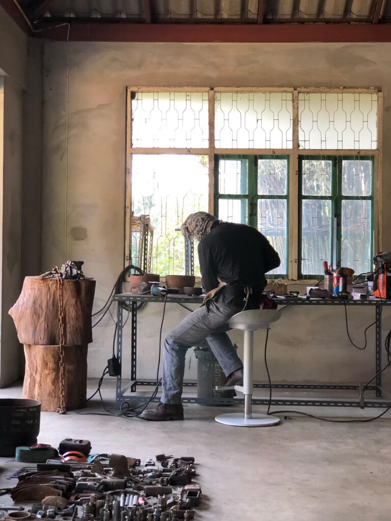 Prakit Seehawong in his studio creating sculptures from scrap metal.