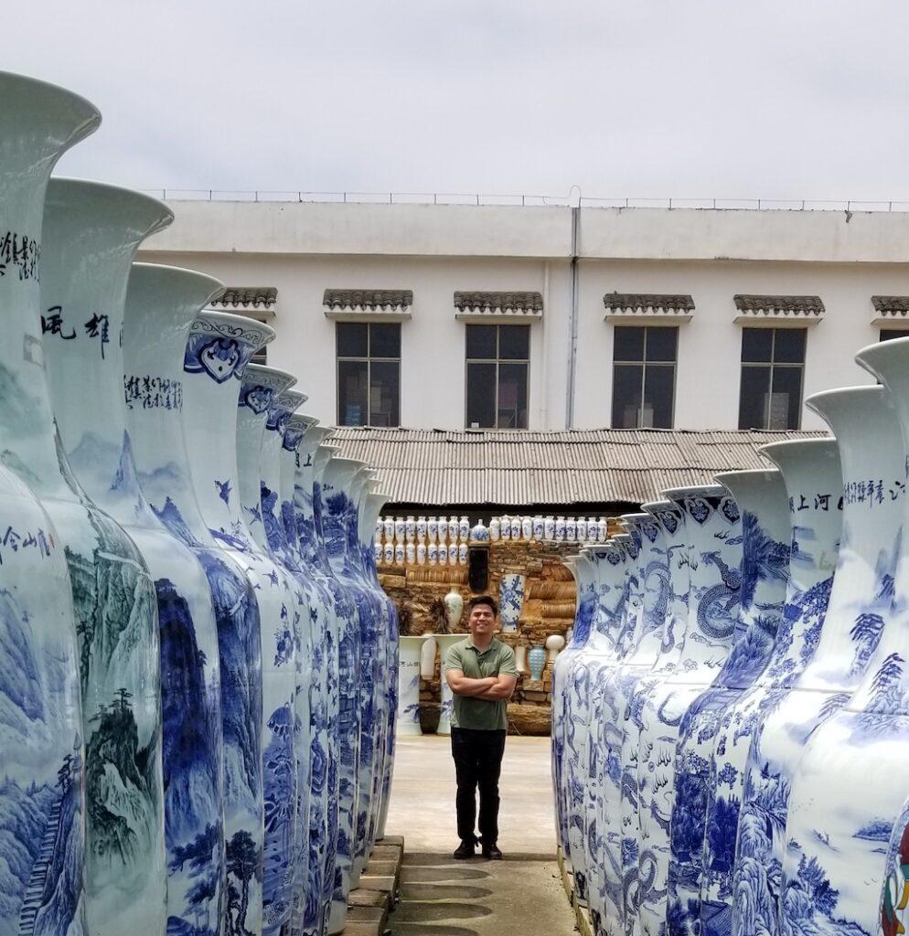 Clarence Mallari dwarfed by Chinese pottery.
